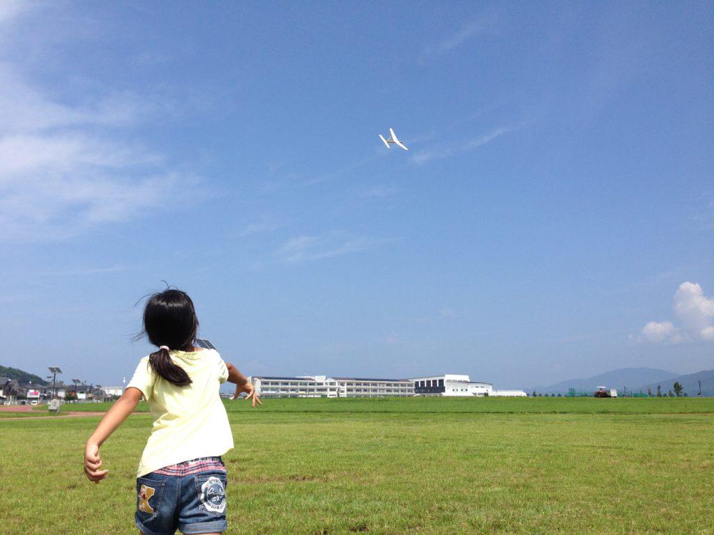 緑地公園で紙飛行機を飛ばす